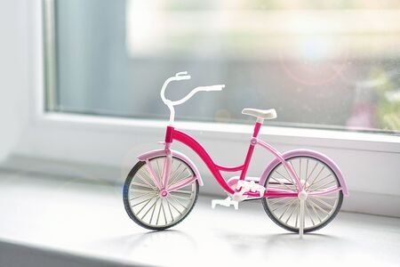 bicycle childrens plastic toy on the windowsill at home. the concept of summer walks Фото со стока