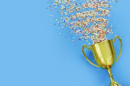 image of little gold cup , concept for winning or success. Golden trophy cup and streamers on blue background, top view with space for text Banco de Imagens