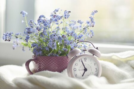 spring bouquet of flowers and a cozy white plaid on the windowsill. pink clock by the window shows morning time Stock Photo