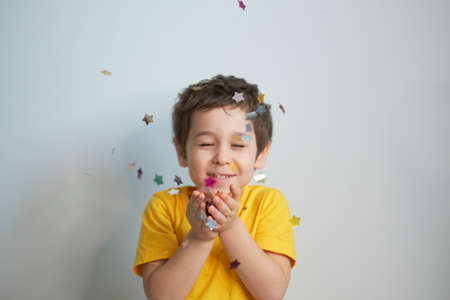 happy birthday child. Photo of charming cute fascinating nice little boy blowing confetti at you to show her festive mood with emotional face expression. Stock Photo
