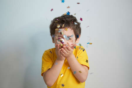 happy birthday child. Photo of charming cute fascinating nice little boy blowing confetti at you to show her festive mood with emotional face expression.