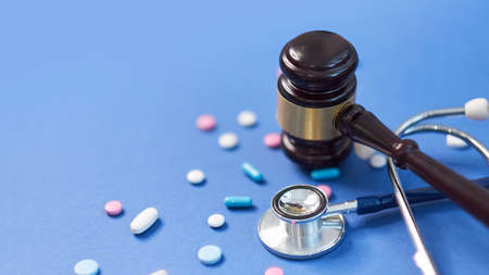 Wooden judge gavel with drugs on table. Space for text. Medical concept. on a blue background. expired drugs. fake market.