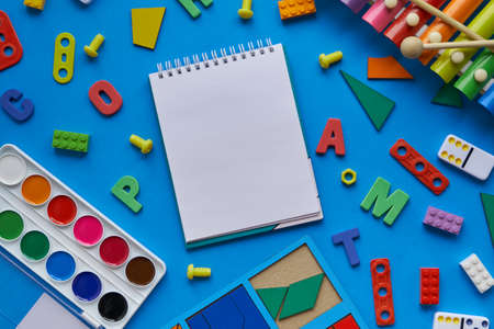 top view background with different subjects for lessons with children. creativity, harmonious growing up of a child. and an open notebook, space for text