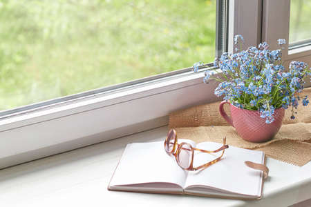 notebook and glasses, spring flowers on wooden rustic windowsill. Photo toned, selective focus. Cozy home still life: spring flowers