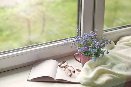 white warm plaid blanket and notebook, glasses on wooden rustic bench. Photo toned, selective focus. Cozy home still life: spring flowers with warm plaid on windowsill