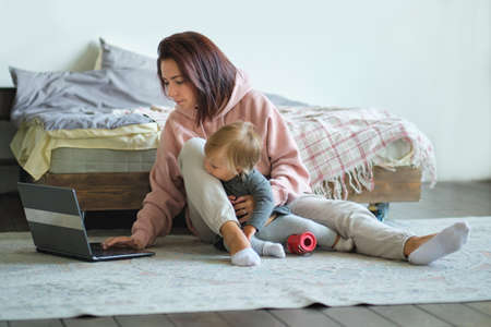 Woman working from home with baby on lap. Mother and Child Parenting Motherhood Love Care Concept