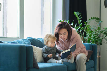 Mother reading a book the baby in sofa. before going to sleep. taking care of children. mothers love for her daughter Reklamní fotografie
