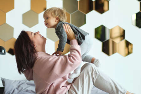 Happy family mother and baby playing, hugging and laughing in bed Reklamní fotografie
