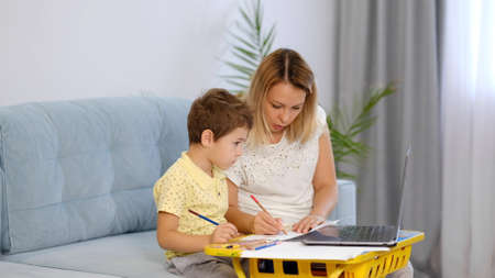 young mother or nanny helps a little boy complete an assignment in an online school. mom and son do school homework together