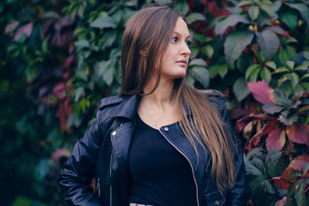 young beautiful woman in a stylish black leather jacket looks to the side, against the background of wild grapes. Autumn portrait in dark tones.