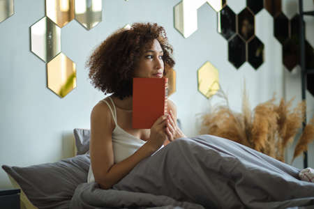 Young black woman sitting in bed and holding a book in his hands. ponders the book he has read, ponders looking aside.