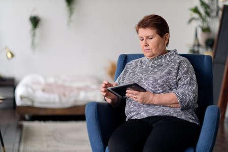 Senior Indian Woman Using Digital Tablet At Home. Banco de Imagens