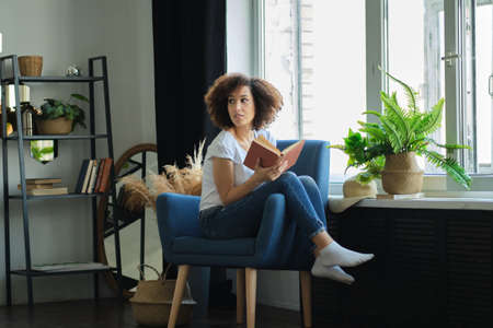 Beautiful young African American woman reading a book lying comfortably on her back on a armchair in the living room in her jeans