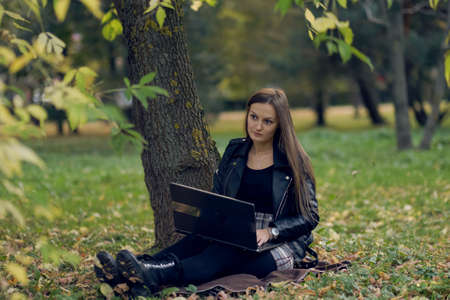 young woman works for a laptop in the park. the student is preparing for exams