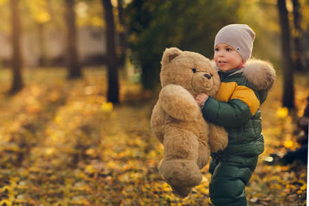 Cute little boy playing outdoors. Happy child walking in autumn park. Toddler baby boy wears trendy jacket. Autumn fashion. Stylish child outside. Stok Fotoğraf
