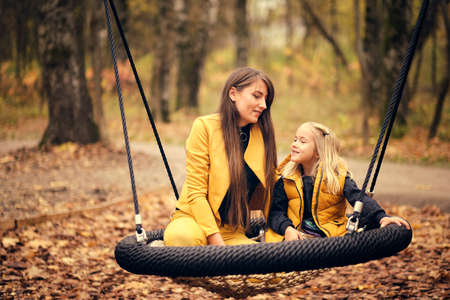 mom and daughter have fun together. young woman and little girl swing on a swing in autumn park