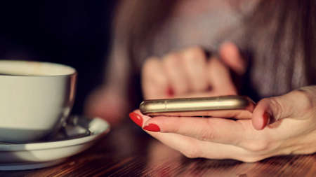 unrecognizable Young woman using smartphone with a coffee cup. Toned picture.