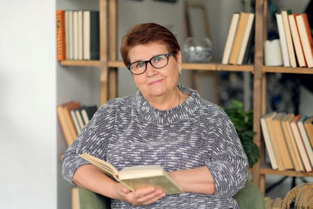 Beautiful old woman in casual clothes reading on couch at home. Beautiful old woman in casual clothes reading on couch at home. Senior woman with poor eyesight in glasses peers into a book.
