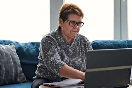 Senior woman using laptop for websurfing. The concept of senior employment, social security. Mature lady sitting at work typing a notebook computer in an home office.
