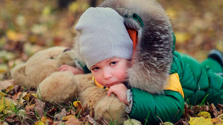 little boy playing with a plush toy in the park. funny baby otty in a warm down jacket and his teddy bear. close up view