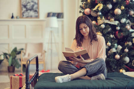 Photo of pretty young lady cuddle paper book. christmas holidays and people concept happy young woman with pencil and notebook writing in bed at home bedroom