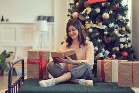 Photo of pretty young lady cuddle paper book. christmas holidays and people concept happy young woman with pencil and notebook writing in bed at home bedroom Imagens