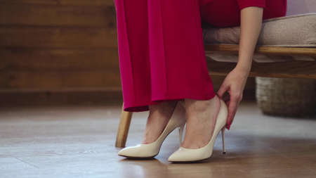 tired business woman takes off her shoes after a long day. swelling of feet after high heels, soft focus. Selective focus. Foto de archivo