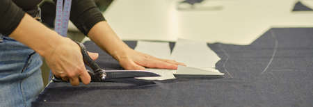 Dressmaker cutting dress fabric on sketch line. Fashion designer tailor or sewer in workshop studio designing new collection clothes. Business owner shop. Horizontal shot. Web Banner 版權商用圖片