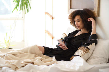 young beautiful african american woman texting on smartphone or watching social network.