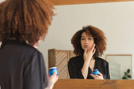 young woman applying cosmetics bathroom. Female looking at face in mirror. Beautiful African American woman apply skincare cream on face.