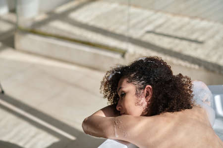 back view curly black girl laying, relaxing in the bath indoors. young woman relaxing in warm bathtub with foam and bubbles. Tired female enjoying rest pamper herself. Stockfoto