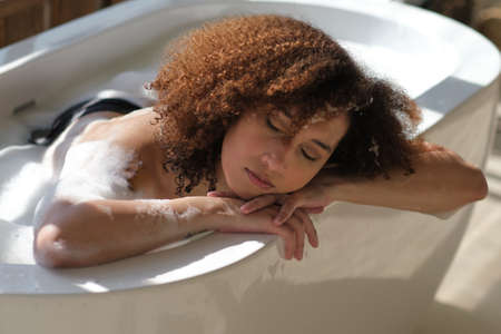 Smiling and relaxing african american woman bathing in a tub full of foam. Amazing time. lifestyle people concept