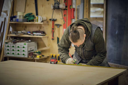 Carpenter holding a measure tape on the work bench. Woodwork and furniture making concept. Carpenter in the workshop marks out and assembles parts of the furniture cabinet