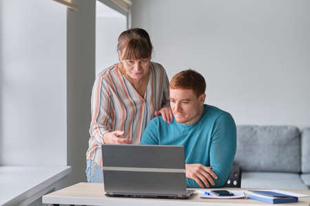 Young Man showing how to use computer to an old woman. elders technology concept. Middle aged man helping his mother use a laptop computer at home, close up
