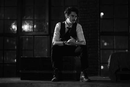 stylish dressed man stands at the window and looks into the distance. pensive man stands at night in a dark room. black and white photography