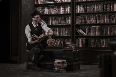 pensive man stands at night in a dark library room and holding a vintage book. stylish man with a mustache straightens the bracelet.