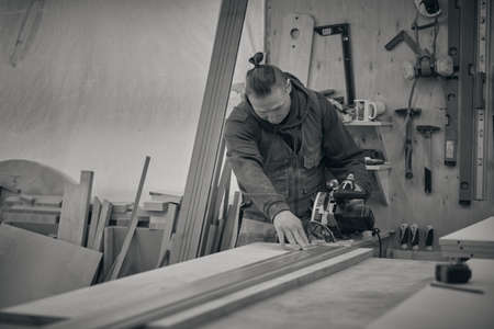 Woodwork and furniture making. Joinery, woodworking and furniture making, professional carpenter cutting wood in carpentry shop, industrial concept