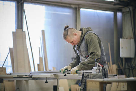 Woodwork and furniture making. Joinery, woodworking and furniture making, professional carpenter cutting wood in carpentry shop, industrial concept.