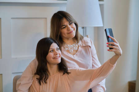 Aged woman and her adult daughter take a selfie on a smartphone. intergenerational relations concept. Family and technology.