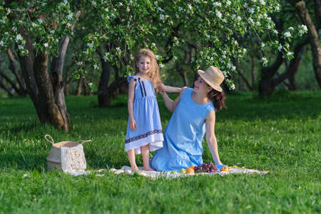 nature scene with family outdoor lifestyle. Mother and little daughter playing together in a park. Happy family concept. Happiness and harmony in family life.