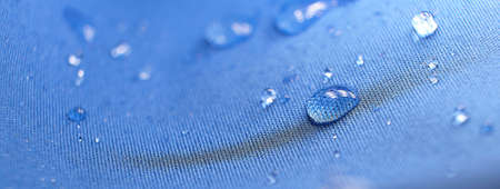Water drops on the fabric. Rain Water droplets on blue fiber waterproof fabric. Water drops pattern over a waterproof cloth. Blue background.