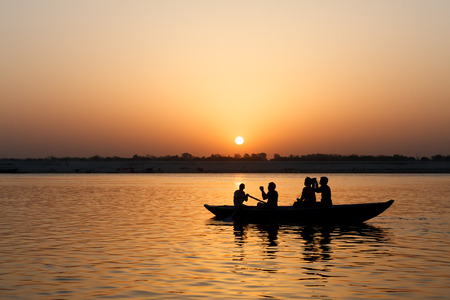 Ganges River and tourists on the boat with rising sun.