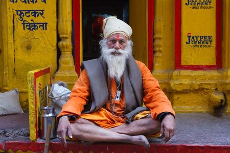 VARANASI,INDIA - March 22,2013 : Unidentified sadhu salutes people and sits on the streets of varanasi