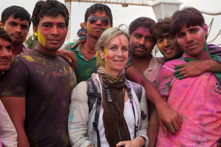 youngs: Mathura,India - 26032013 : Colorful Holi Festival time , an European woman together with Indian young in the streets of Mathura,India