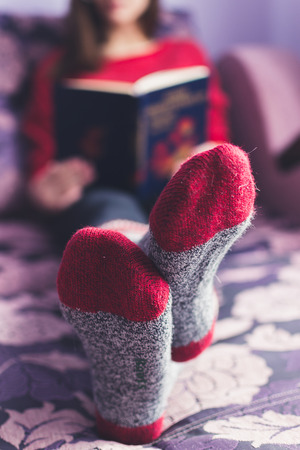 girl reading a book in a warm blanket Stock Photo