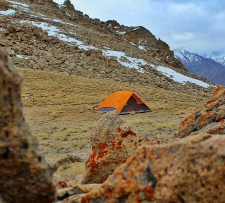 orange color tent being set up by trekkers for night stay in ladakh 스톡 콘텐츠