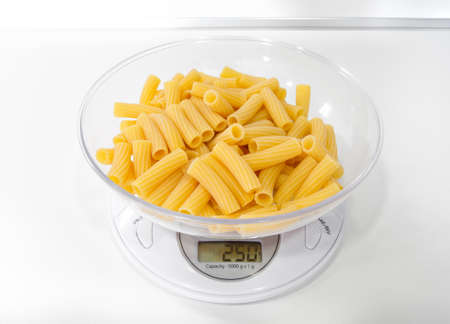 Uncooked pasta maccheroni on the kitchen scale without any kind of sauce. 250 grams is the ideal quantity of pasta for a family of three persons. Always weigh the carbohydrates before cooking.