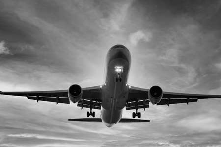 Very close-up of an airplane seen from below while landing at low altitude. Frontal view of a wide body aircraft with black and white filter. Really close perspective of long haul jet with gear down