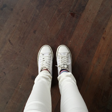 denim jeans: White Sneakers shoes walking on ground top view great for any use.