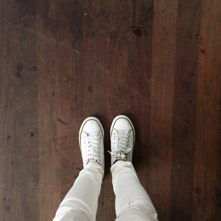 denim: White Sneakers shoes walking on ground top view great for any use.